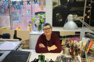 Bianka Guna posing at her desk in her studio space