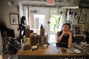Artist sitting behind sales counter